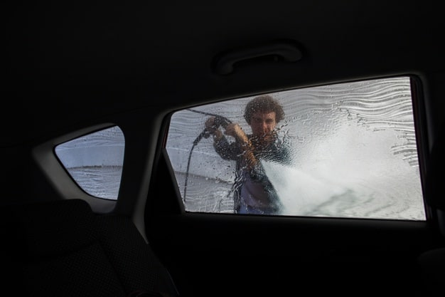 man cleaning with water car window