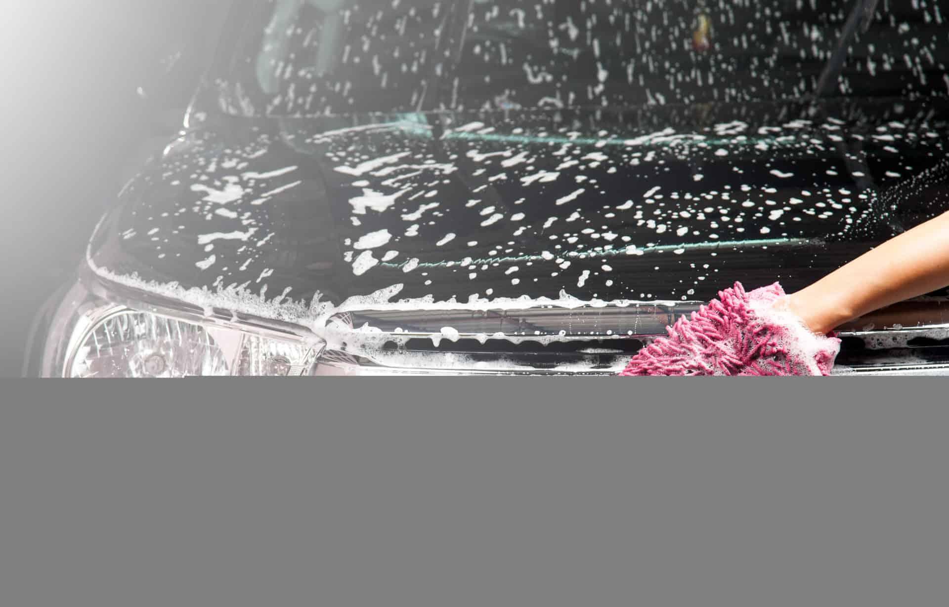 man washing a soapy black car with a cloth