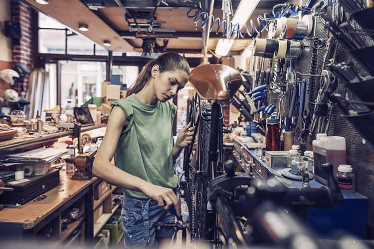 Rapariga a realizar a manutenção da bicicleta