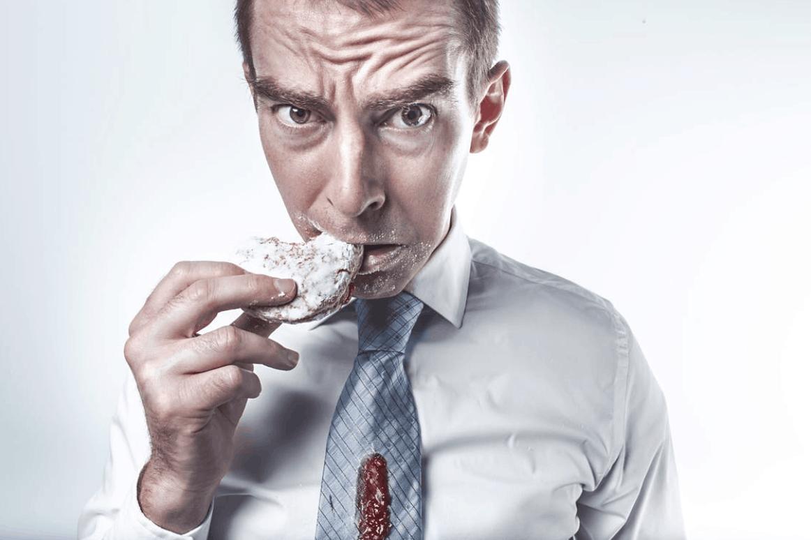 Muž, ktorý je nezdravé jedlo akvapká mu omáčka